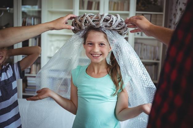 Mädchen imitiert, um ein engel zu sein, indem es eine luftpolsterfolie und einen ausgepackten ring trägt