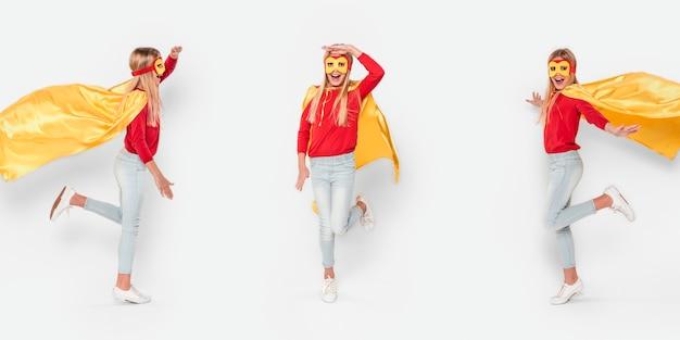 Mädchen in anderer haltung, die heldenkostüm trägt