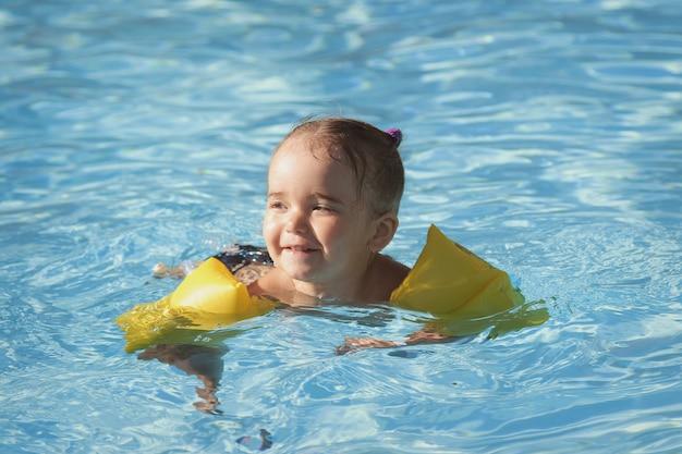 Mädchen in armlehnen zum schwimmen im urlaub im pool. spa, schwimmunterricht, urlaub, wasseraufbereitung