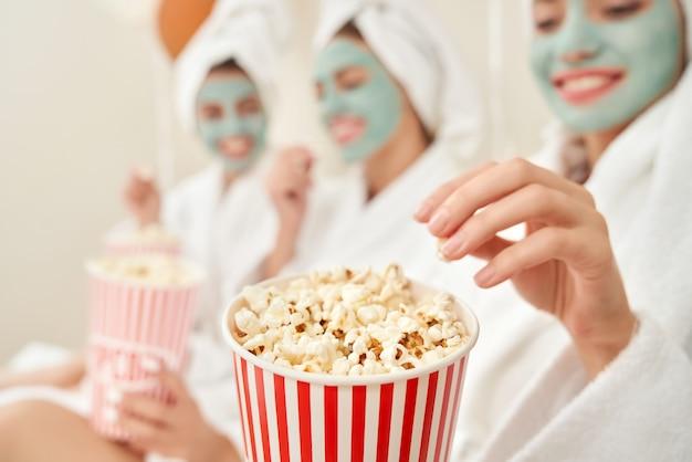 Mädchen in bademänteln, die popcorn essen.