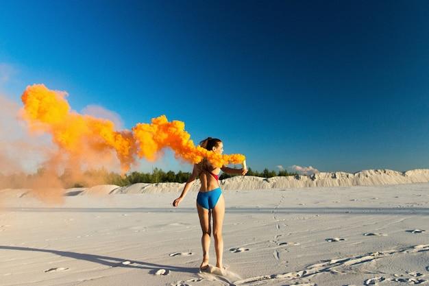 Mädchen in blau schwimmen-anzug tänze mit orange rauch am weißen strand
