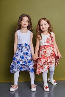 Mädchen in blumenkleidern händchen haltend