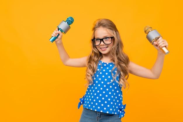 Mädchen in brille winkt mit mikrofonen an einer orangefarbenen wand