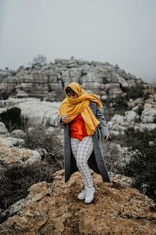 Mädchen in den bergen mit einem gelben schal