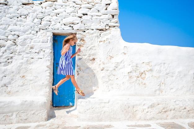 Mädchen in den blauen kleidern, die spaß draußen auf mykonos-straßen haben