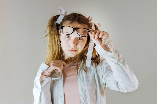 Mädchen in den brillen, die ihr haar betrachtet kamera halten