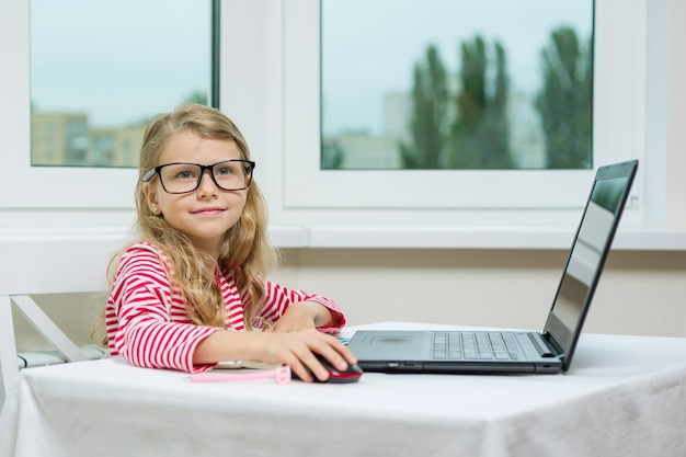 Mädchen in den erwachsenen gläsern sitzt am tisch mit computer