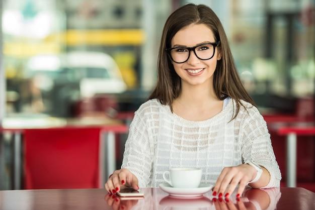 Mädchen in den gläsern und in weißem pullover, die im städtischen café sitzen.