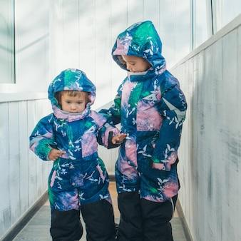 Mädchen in den gleichen warmen overalls. winterkleidung für kinder jeden alters