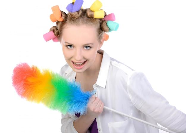 Mädchen in den haarrollen mit einem abstaubungsgerät.