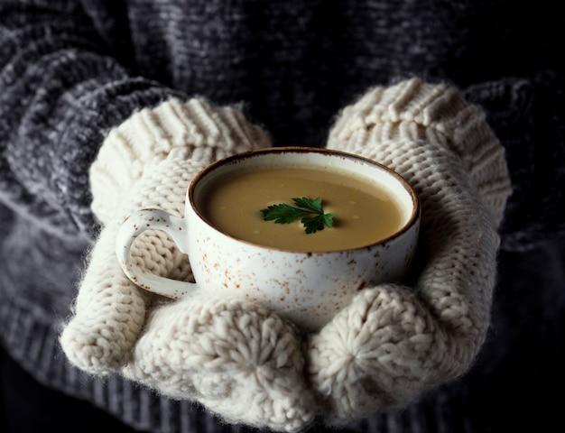 Mädchen in den handschuhen, die eine schale suppe anhalten