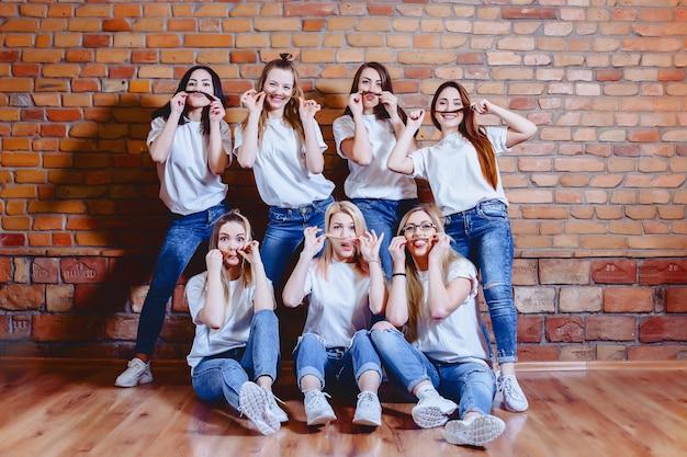 Mädchen in den jeans am hintergrund der backsteinmauer