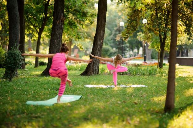 Mädchen in den rosa sportanzügen, die yoga im park üben