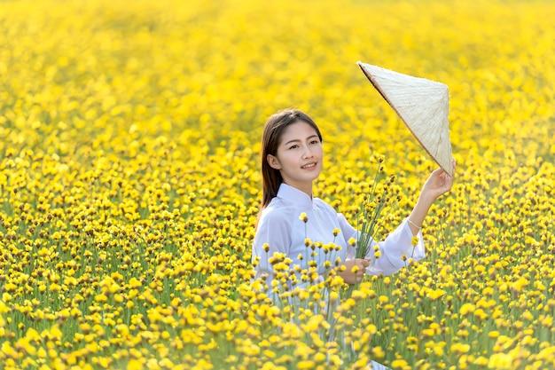 Mädchen in den traditionellen vietnamesischen nationalen kostümen, die auf dem gelben blumengebiet spielen
