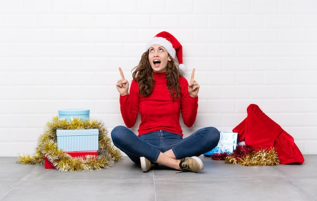 Mädchen in den weihnachtsfeiertagen sitzend auf dem boden, der mit dem zeigefinger eine großartige idee zeigt