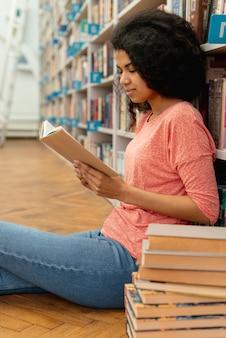 Mädchen in der bibliothek auf dem boden lesen
