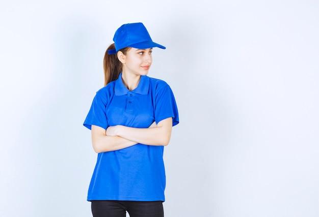 Mädchen in der blauen uniform, die arme kreuzt und introvertierte posen gibt.