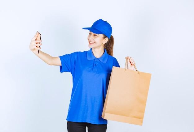 Mädchen in der blauen uniform, die eine pappeinkaufstasche hält und mit dem telefon spricht.