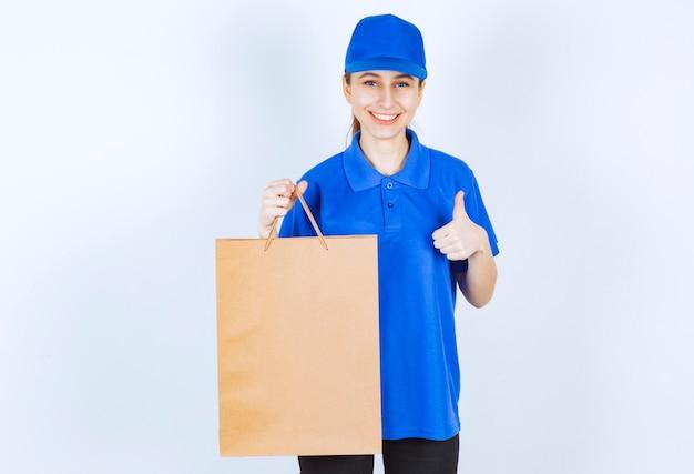 Mädchen in der blauen uniform, die eine pappeinkaufstasche hält und zufriedenheitszeichen zeigt.
