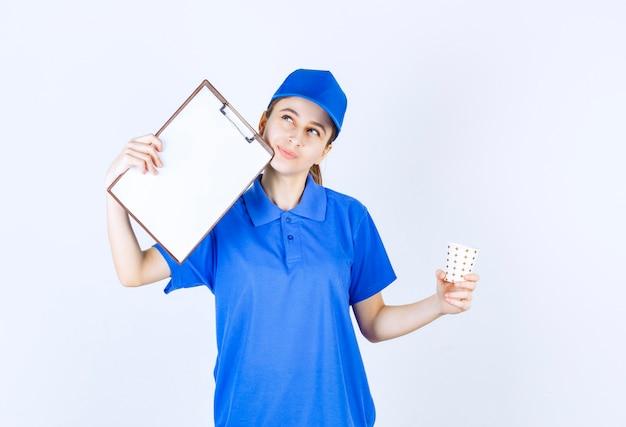 Mädchen in der blauen uniform, die eine tasse getränk hält und den rohling zur unterschrift präsentiert.