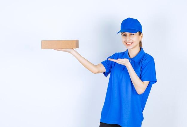 Mädchen in der blauen uniform, die einen karton zum mitnehmen hält.