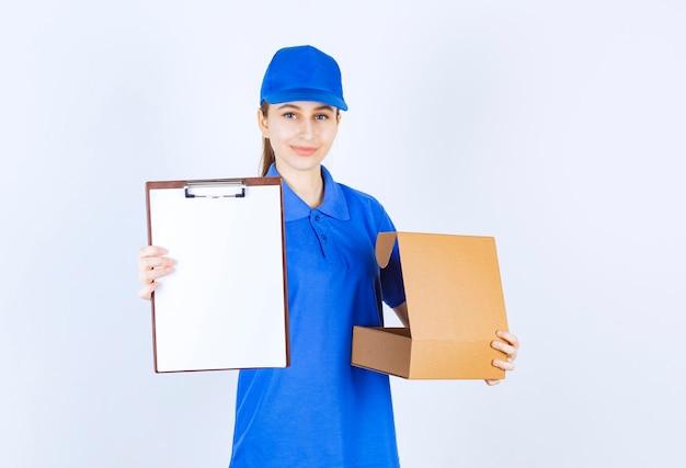 Mädchen in der blauen uniform, die einen offenen pappkarton zum mitnehmen hält und um singatur bittet.