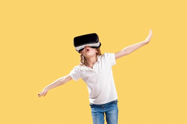 Mädchen in der formalen ausstattung, die die vr-gläser einsetzen trägt, teilt in die lokalisierte aufregung aus. kind, das ein spielgerät für virtuelle realität verwendet. virtuelle technologie