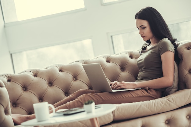 Mädchen in der freizeitkleidung benutzt einen laptop beim zu hause arbeiten.