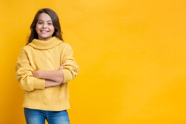 Mädchen in der gelben strickjacke mit den gekreuzten händen
