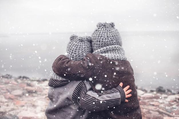 Mädchen in der gestrickten grauen mütze, die ihren gefrorenen kleineren bruder umarmt