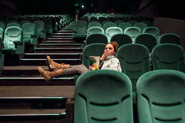 Mädchen in der großen kinohalle mit popcorn
