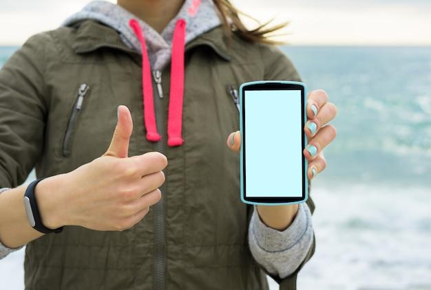 Mädchen in der grünen jacke am strand, der den handyschirm zeigt