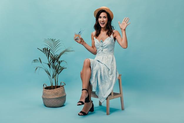 Mädchen in der guten stimmung genießt cocktail auf blauem hintergrund mit palme