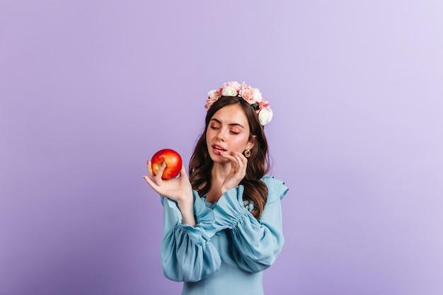 Mädchen in der guten stimmung schaut auf köstlichen roten apfel. schnappschuss der frau in der blauen bluse an der isolierten wand.