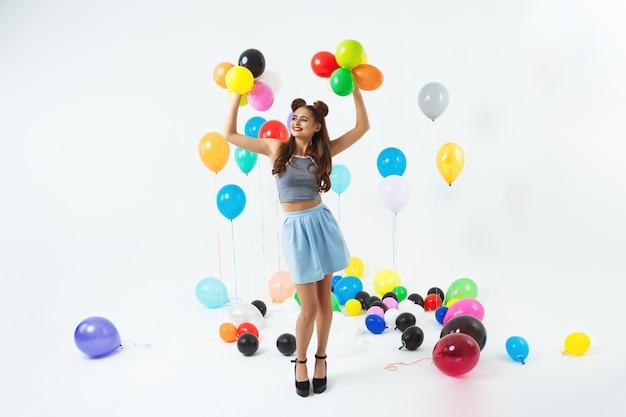 Mädchen in der hipster-kleidung, die hände mit kleinen luftballons hochhält