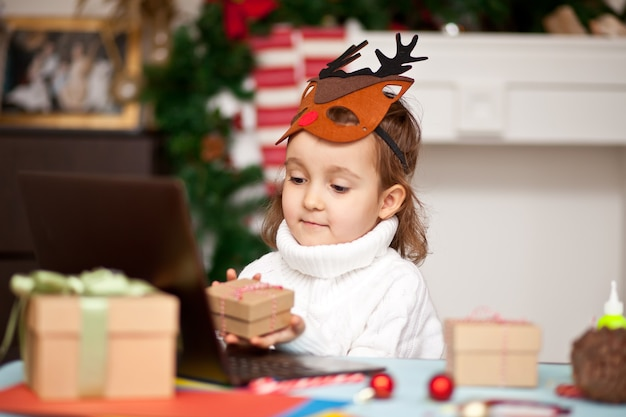 Mädchen in der hirschmaske, die eine geschenkbox hält und ein digitales tablet-laptop-notizbuch verwendet