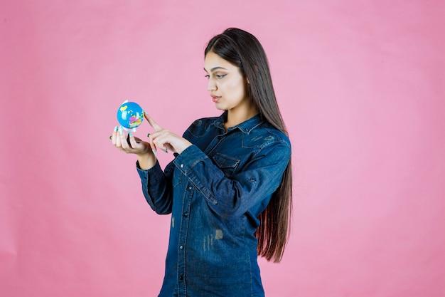 Mädchen in der jeansjacke, das orte auf dem globus errät