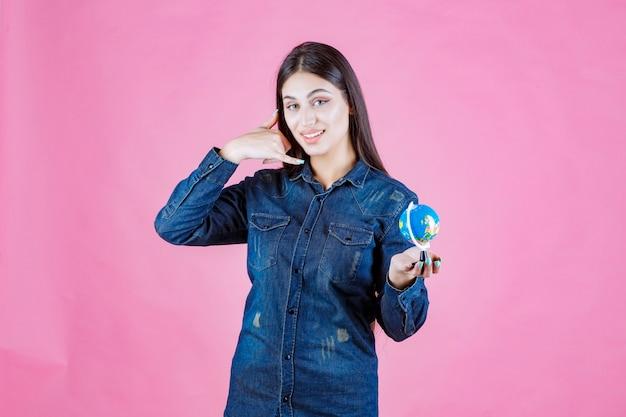 Mädchen in der jeansjacke, die einen mini-globus hält und bittet, anzurufen