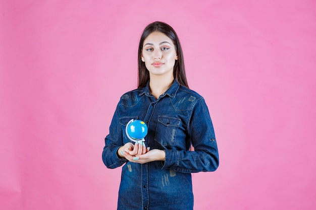 Mädchen in der jeansjacke, die einen mini-globus in ihrer handfläche hält