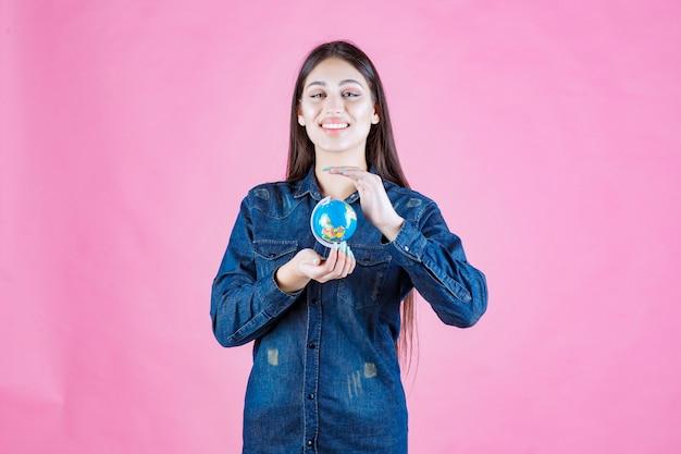 Mädchen in der jeansjacke, die einen mini-globus zwischen ihren händen hält