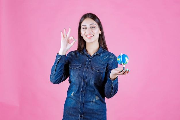 Mädchen in der jeansjacke, die gutes handzeichen macht