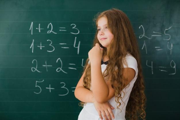 Mädchen in der klasse denken und lächelnd