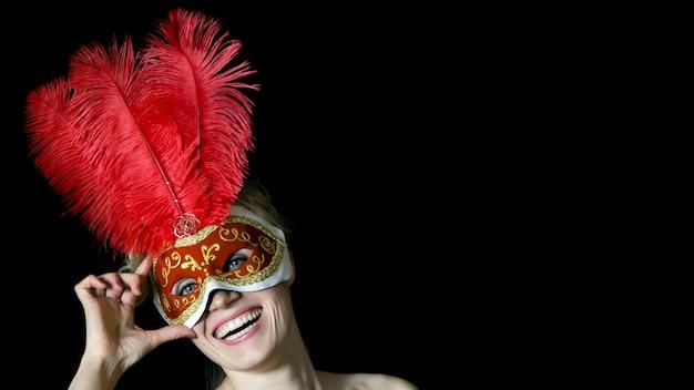 Mädchen in der maske mit federn am karneval.
