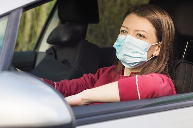 Mädchen in der medizinischen maske, die ein auto fährt. fahrerin mit persönlicher schutzausrüstung.