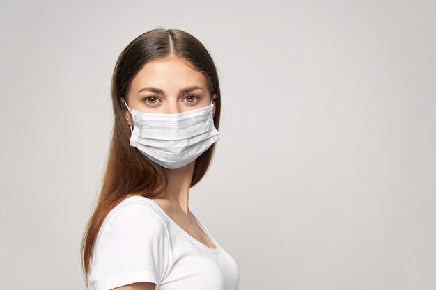 Mädchen in der medizinischen maske schaut nach vorne und isolierter hintergrund und nahaufnahme