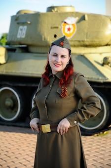Mädchen in der militäruniform auf dem panzerhintergrund