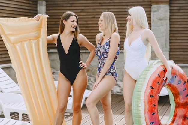Mädchen in der nähe eines pools. freunde in einem stylischen badeanzug. damen in den sommerferien.