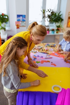 Mädchen in der nähe von lehrer. nettes dunkelhaariges mädchen, das beim malen auf gelbem papier in der nähe des lehrers steht painting