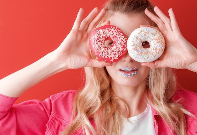 Mädchen in der rosa jacke auf rotem hintergrund mit donut in den händen