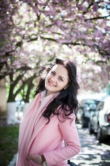 Mädchen in der rosa kleidung mit kirschblüte-blume im haar, das unter dem kirschblüte-baum aufwirft